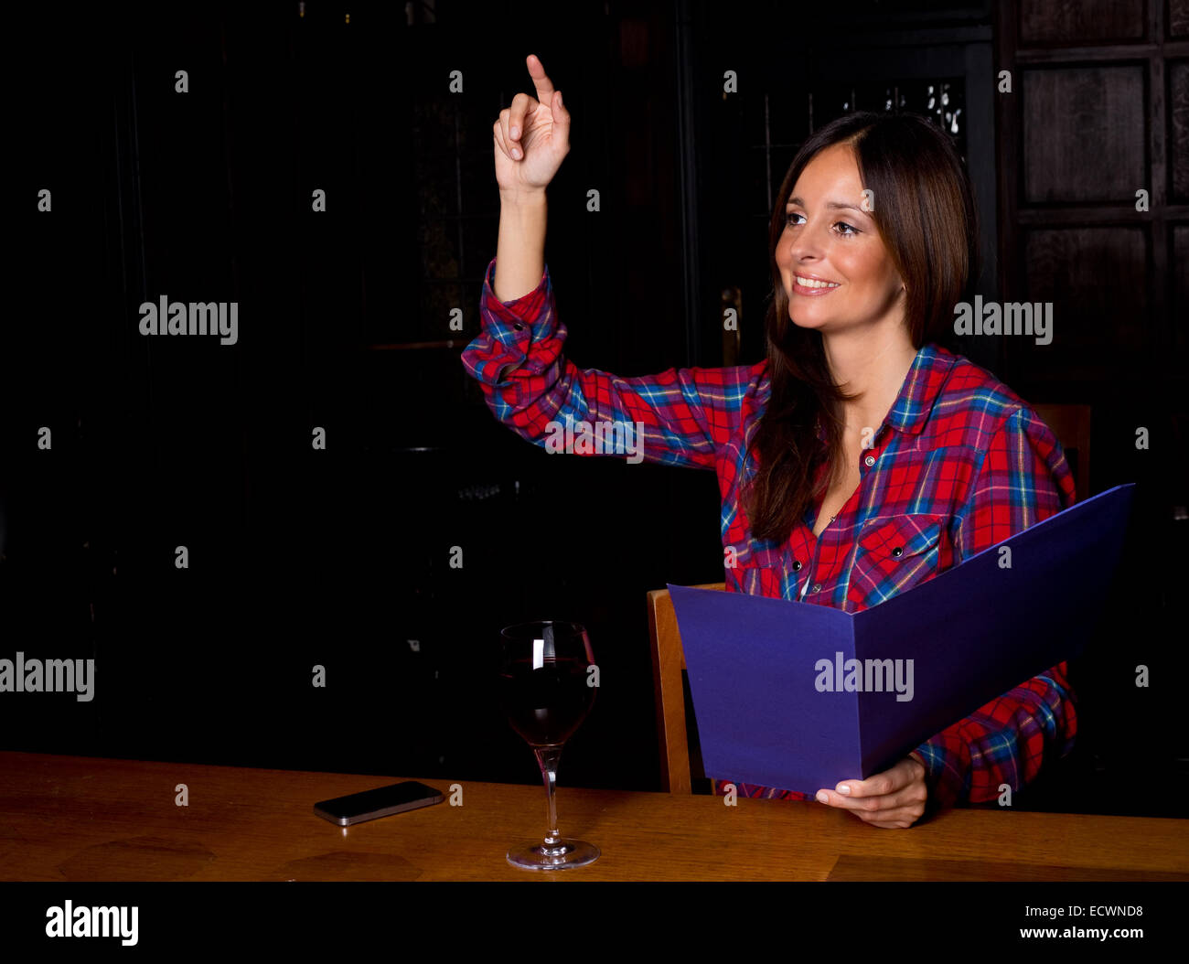 young woman looking at a menu. - Stock Image