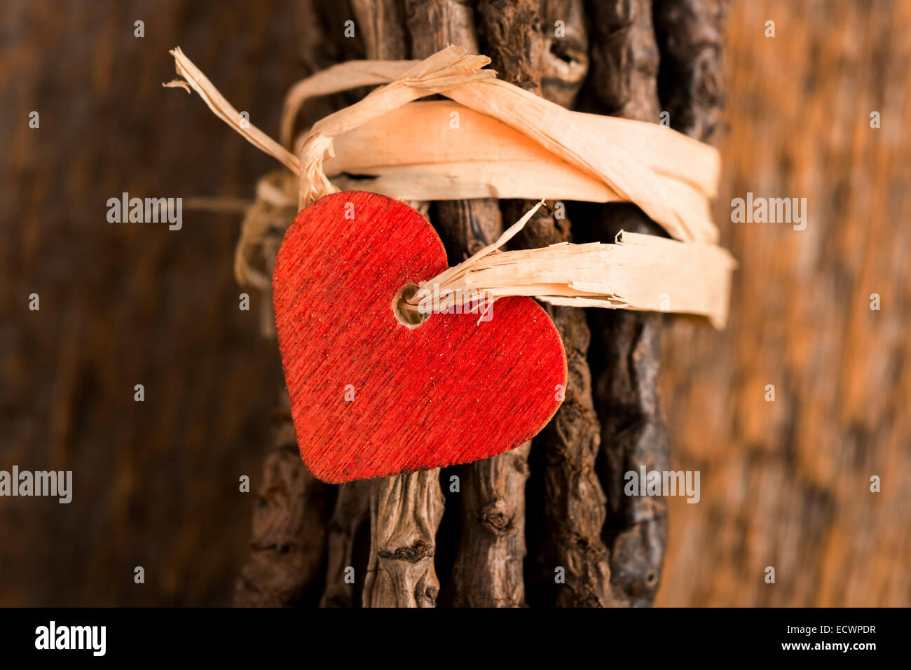 Wood red heart attached with twine to  wrapped twigs set on rustic wood - Stock Image