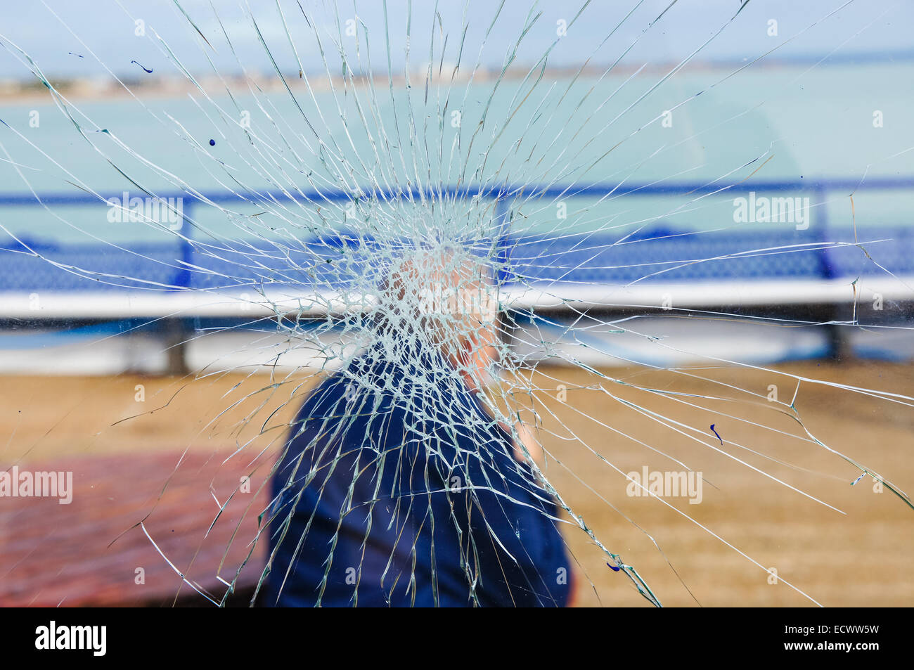 old man sitting behind the window with cracked glass, conceptual image for aging process - Stock Image