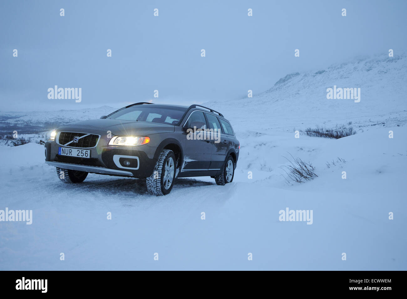 Car driving on snow and ice near the arctic circle in Sweden. Volvo XC70 using winter tyres - Stock Image