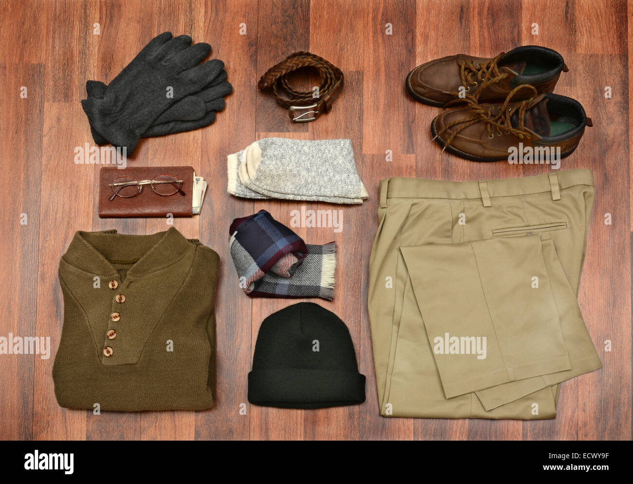 High angle shot of men's winter clothes laid out on a dark wood floor. Items include, Sweater, Scarf, Gloves, - Stock Image