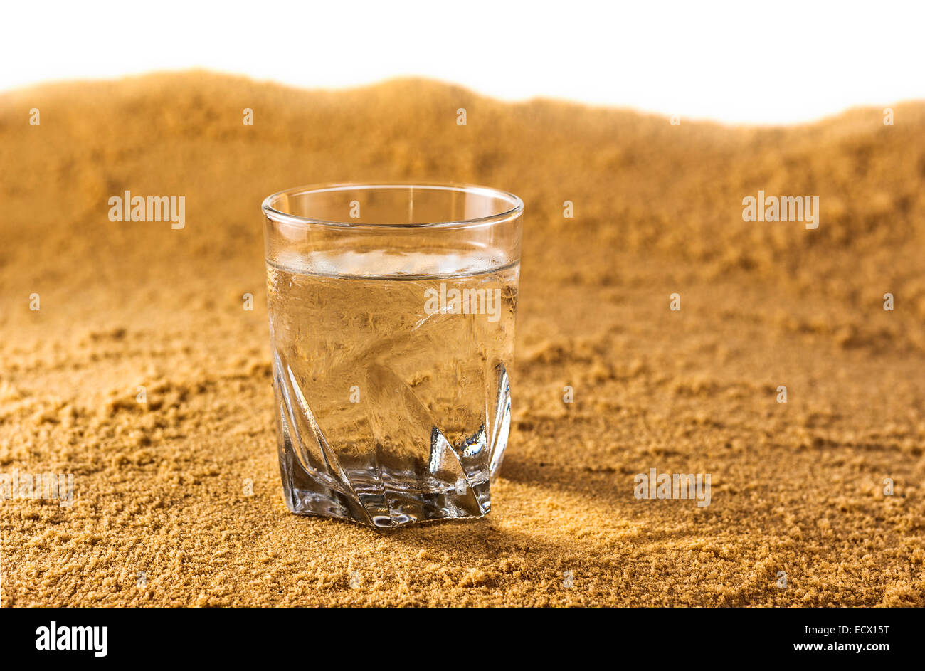 Glass of cold, clear water in a desert. - Stock Image