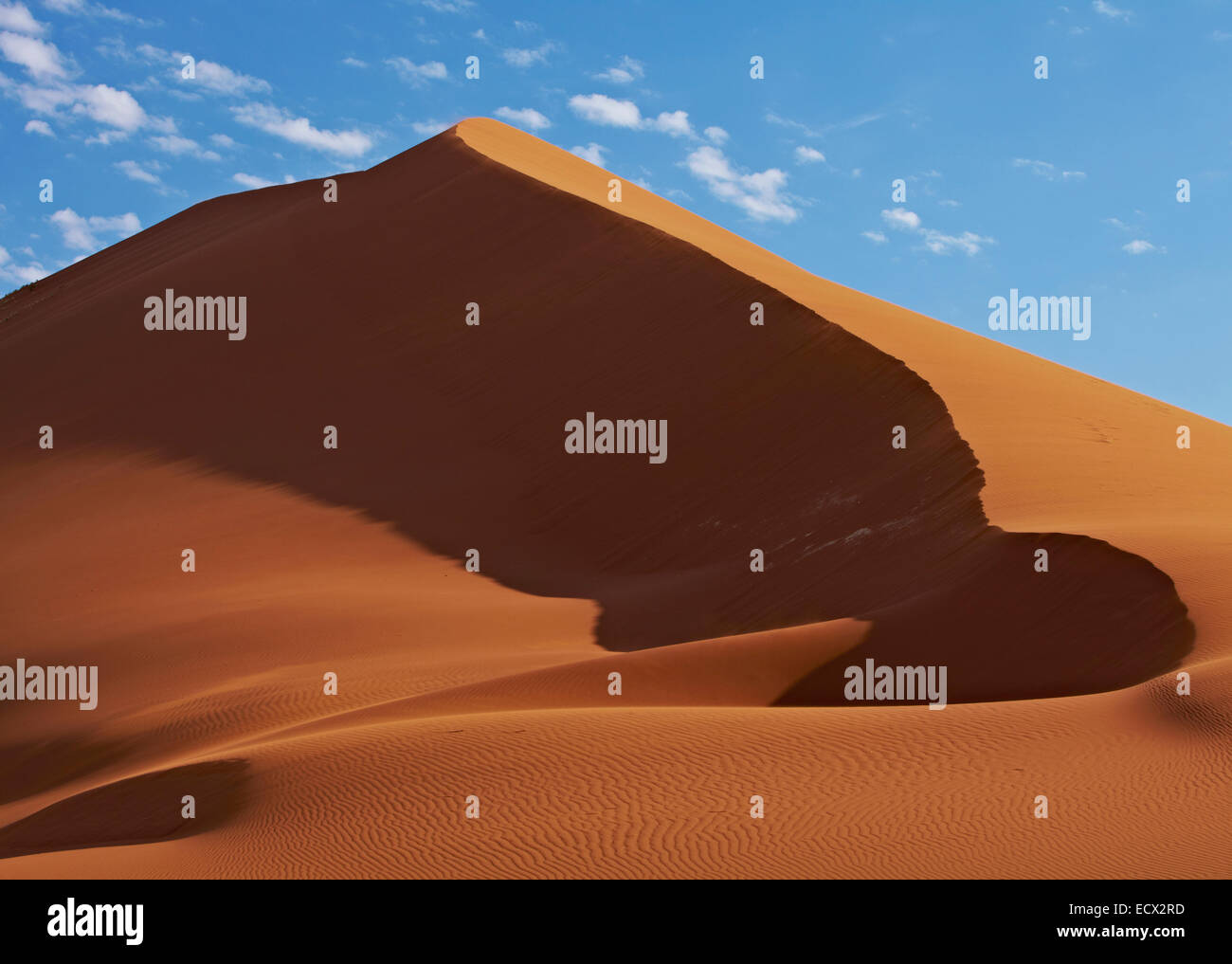 View of sand dunes in desert with blue sky and clouds in background - Stock Image