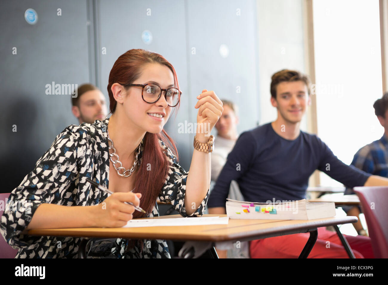 University student taking notes and listening during seminar in classroom - Stock Image
