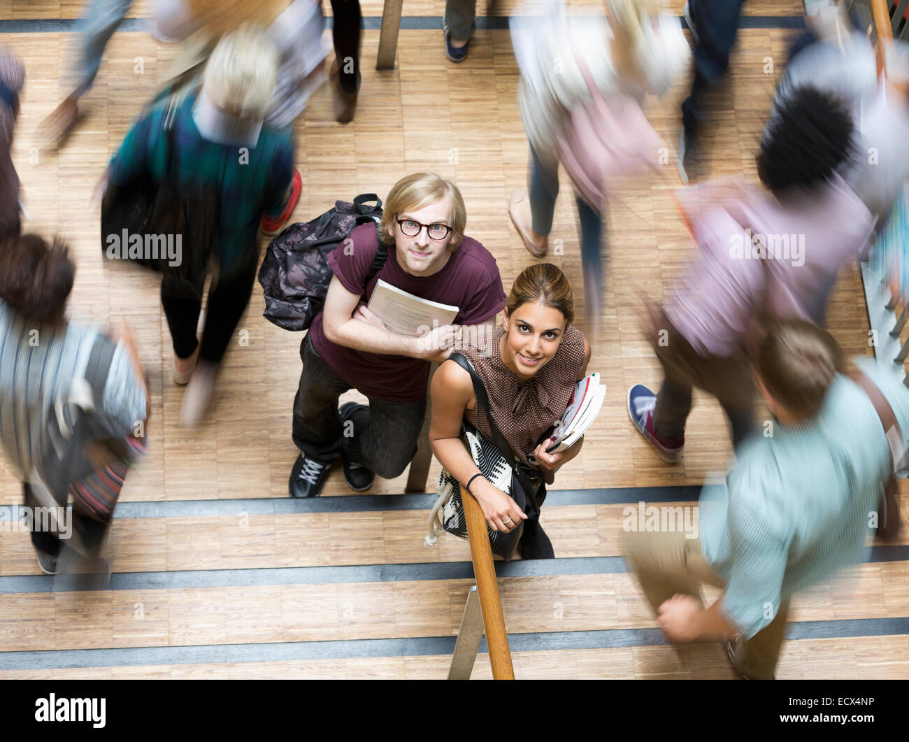 Male and female students looking at camera and standing in corridor during break Stock Photo