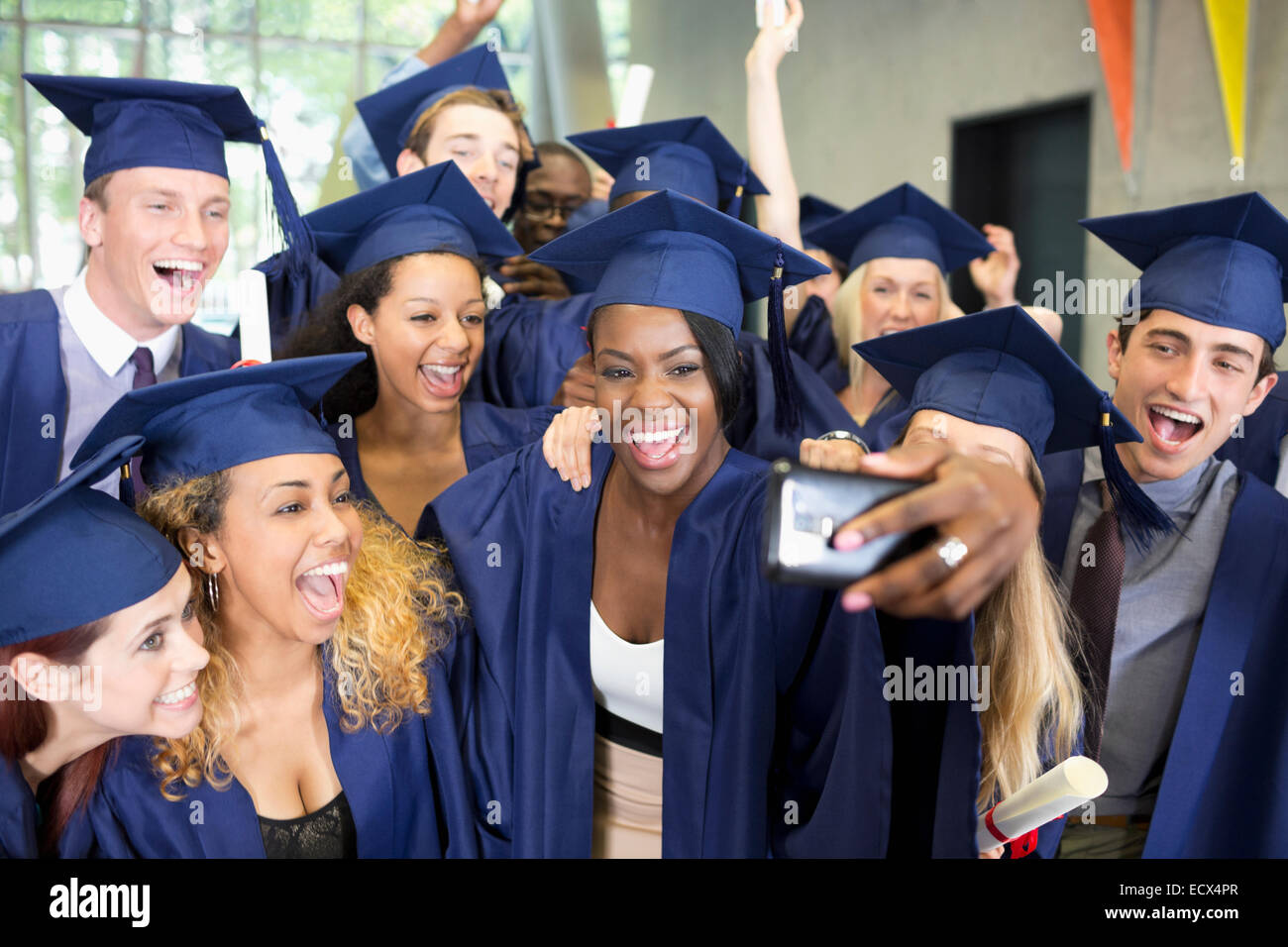 fce17a23253 Group of smiling students in graduation gowns taking selfie on graduation  day - Stock Image