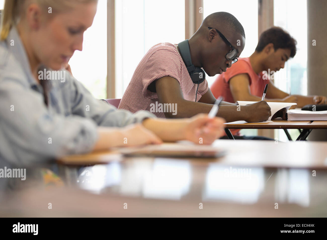 View of students sitting at desks during test in classroom - Stock Image
