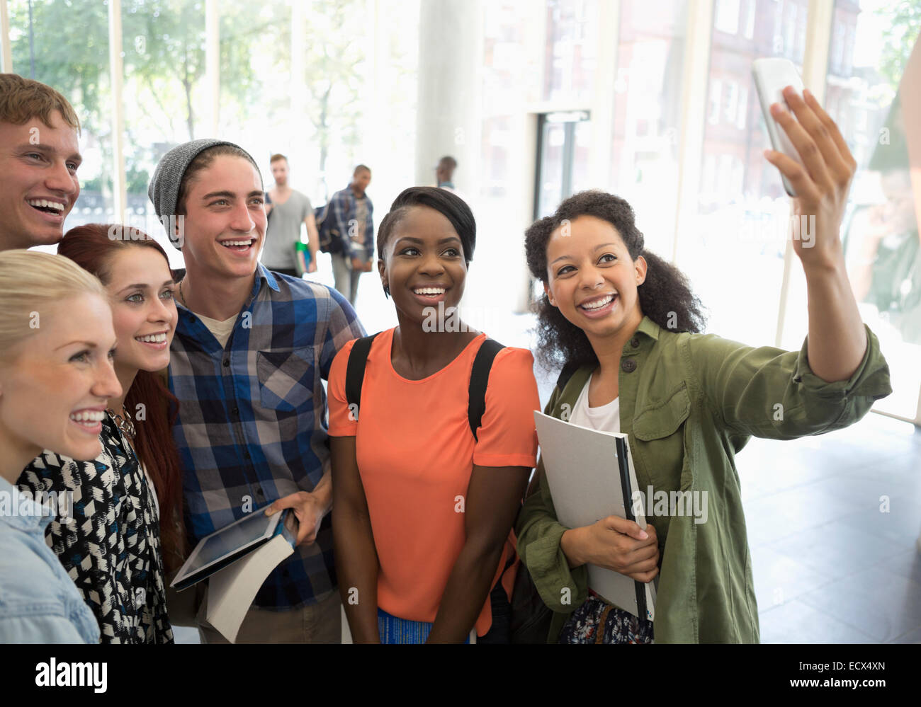 Group of smiling students holding books and digital tablet, taking selfie with smart phone Stock Photo