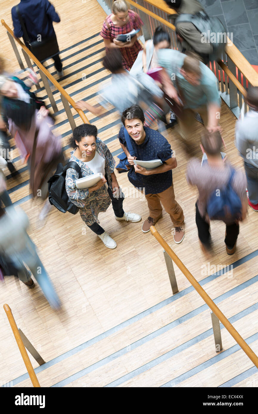 Elevated view of two smiling students standing on stairs with other students going up and down - Stock Image
