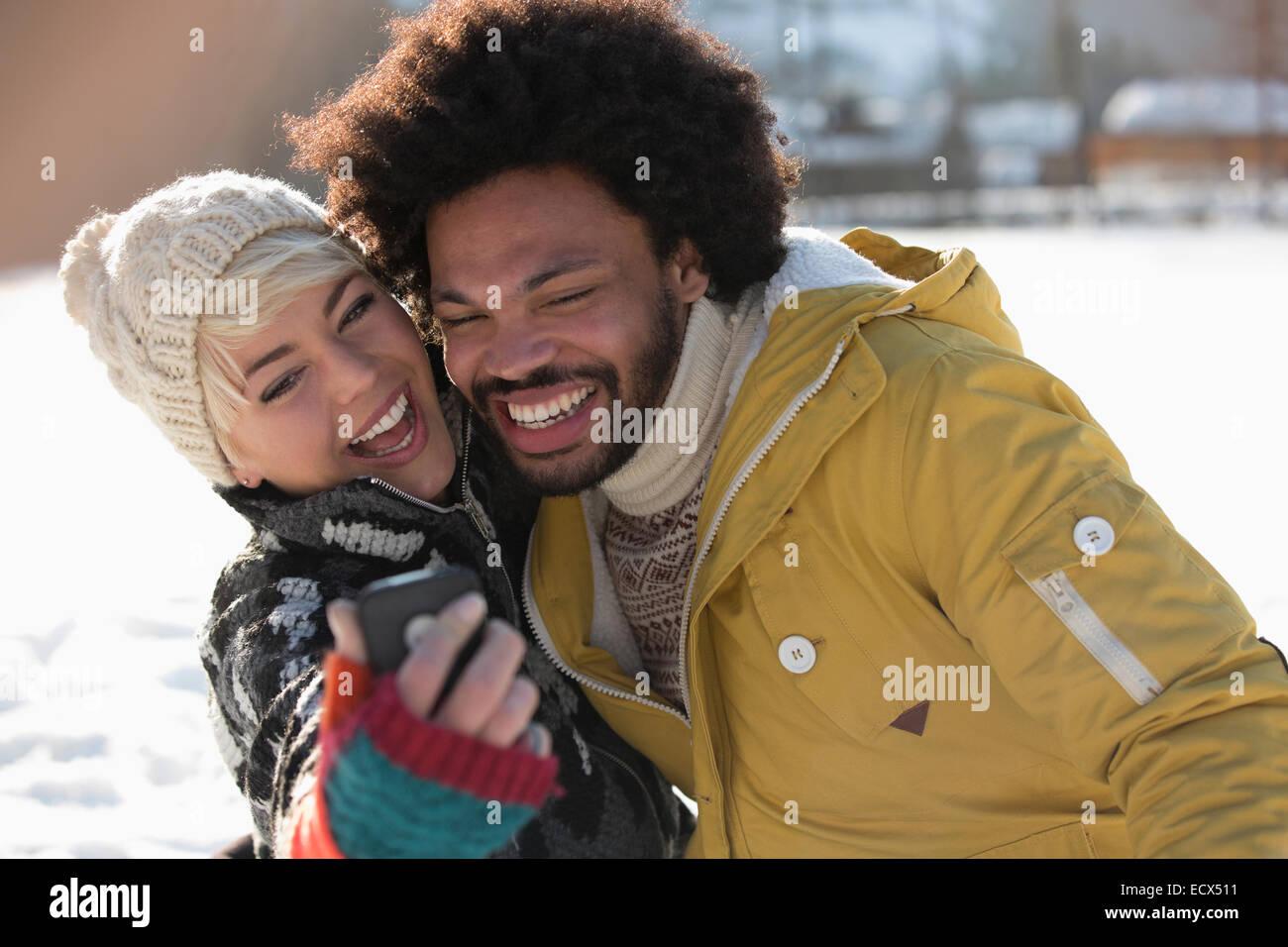 Happy couple taking selfie in snow - Stock Image