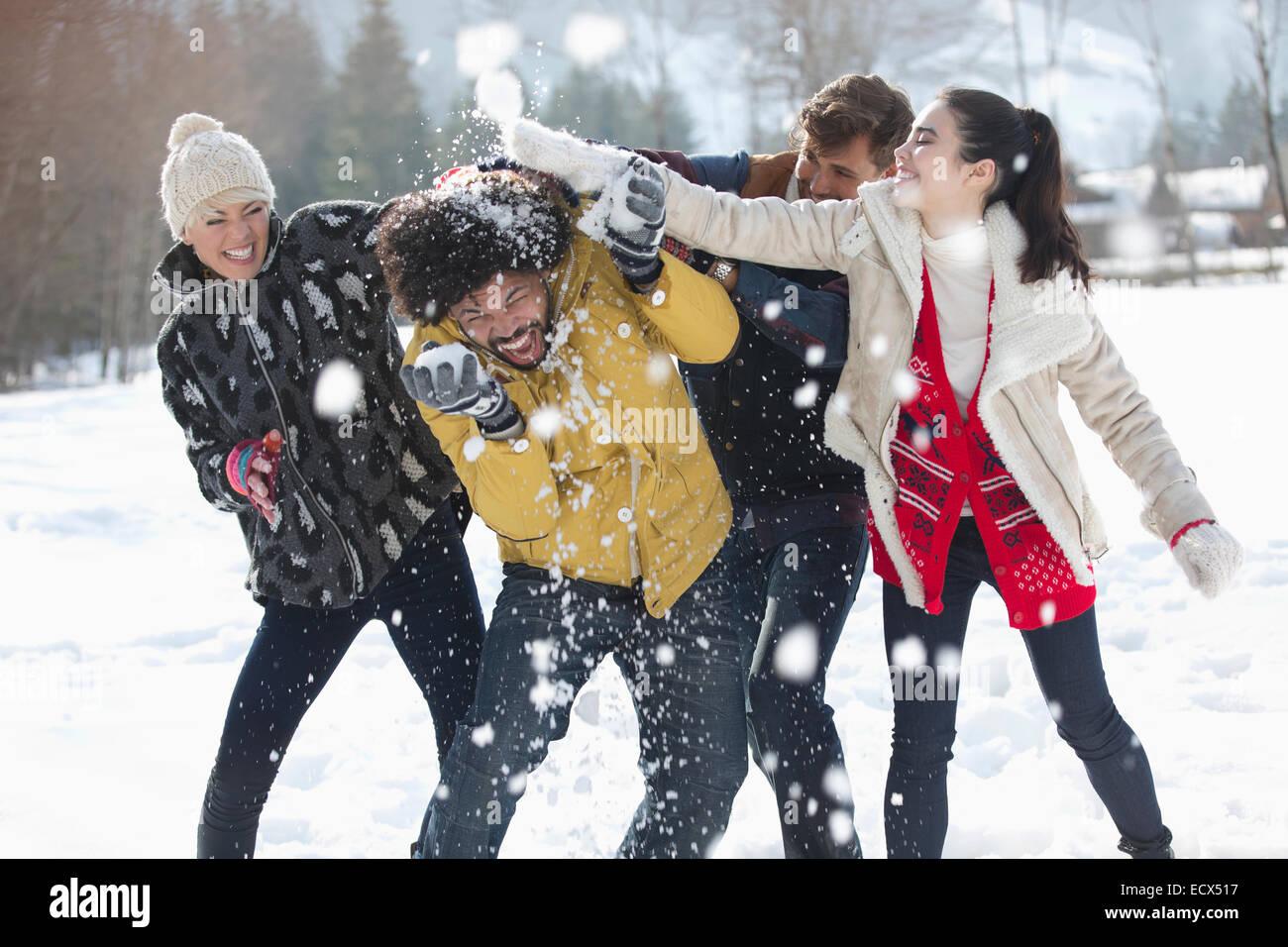 Friends enjoying snowball fight - Stock Image