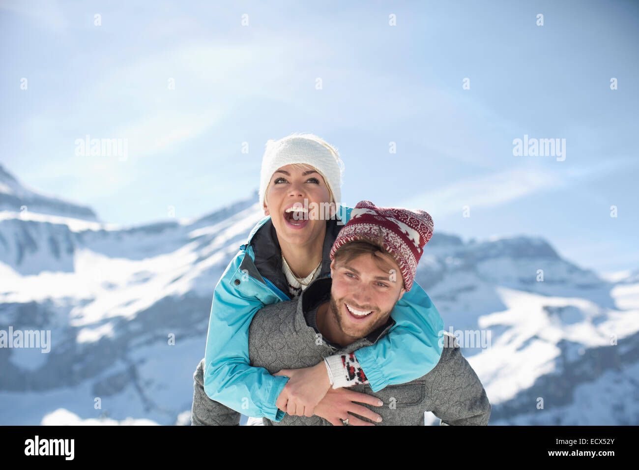 Couple piggybacking at mountains - Stock Image