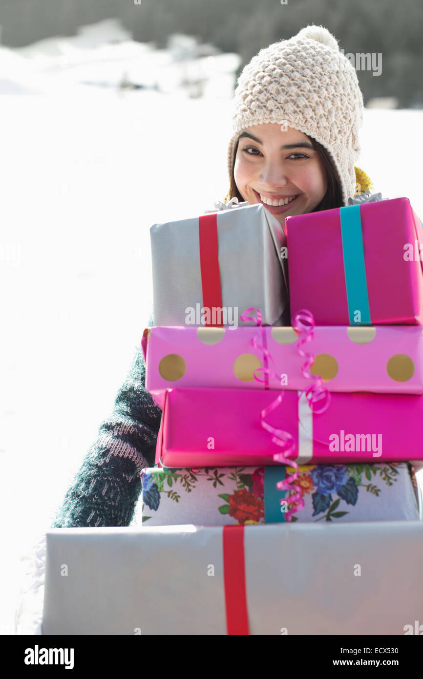 Portrait of smiling woman carrying stack of gifts - Stock Image