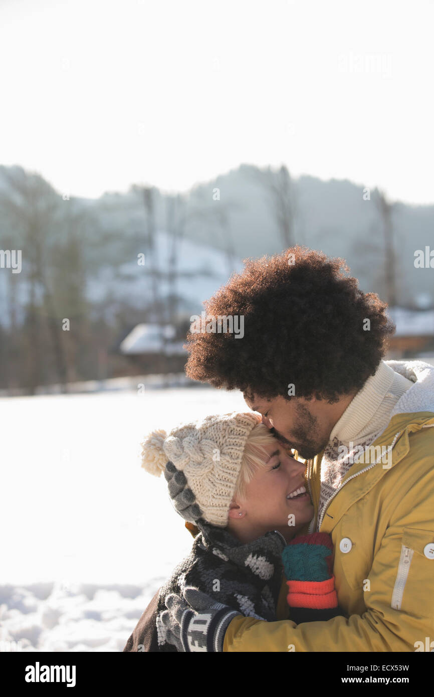 Man kissing woman's forehead in snow - Stock Image