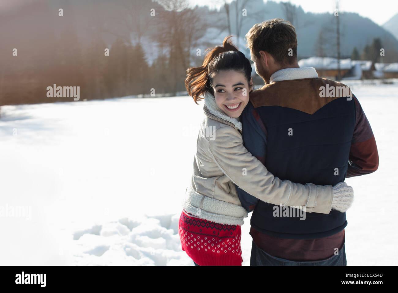 Happy couple walking in snow - Stock Image