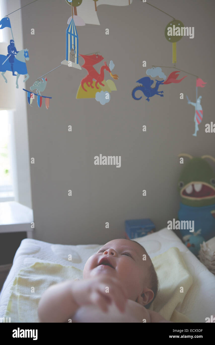 Little baby lying down and looking at colorful hanging mobile - Stock Image