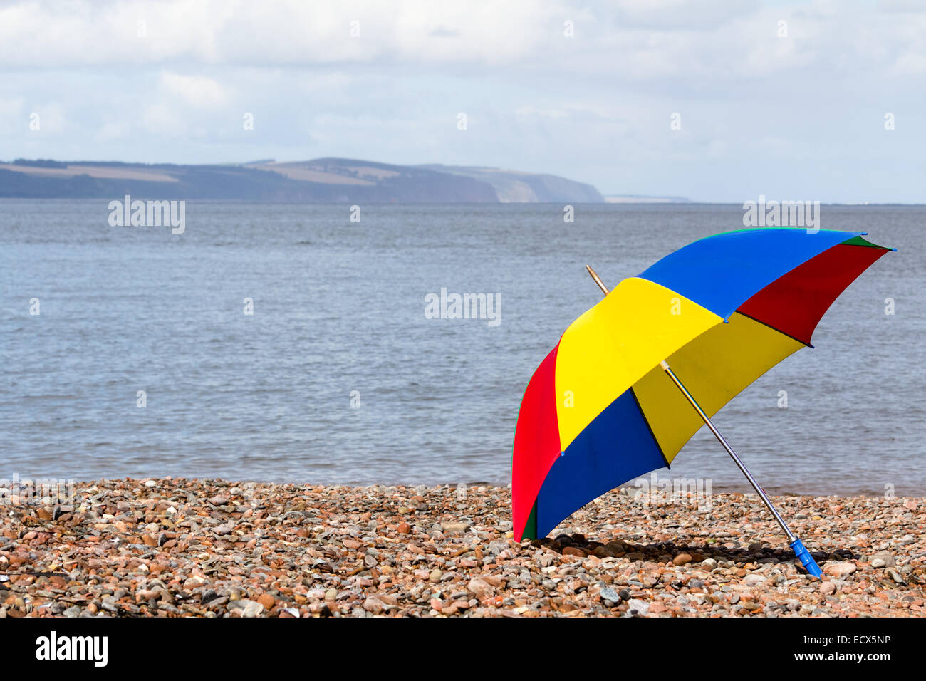 A colorful open rain umbrella at the beach of Channonry Point, Scotland - known for dolphin watching - Stock Image