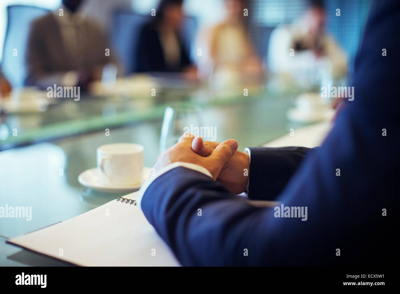 Businessman sitting at conference table in conference room with hands clasped - Stock Image