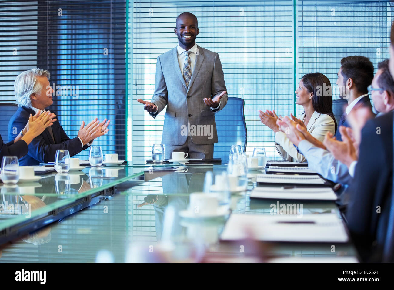 Businessman giving speech in conference room, colleagues clapping hands - Stock Image