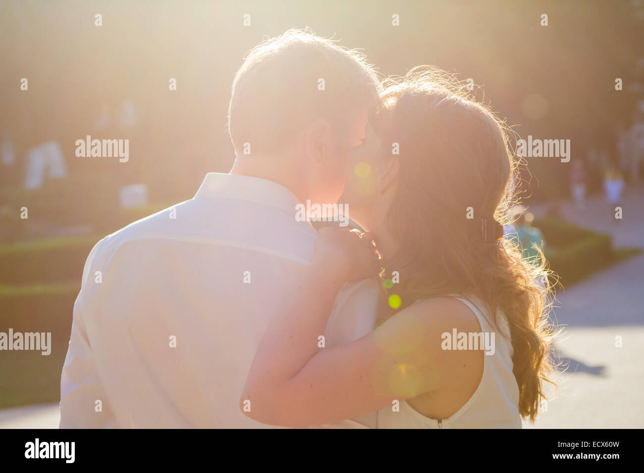 Two lovers - she is whispering something in his ear and he is listening Stock Photo