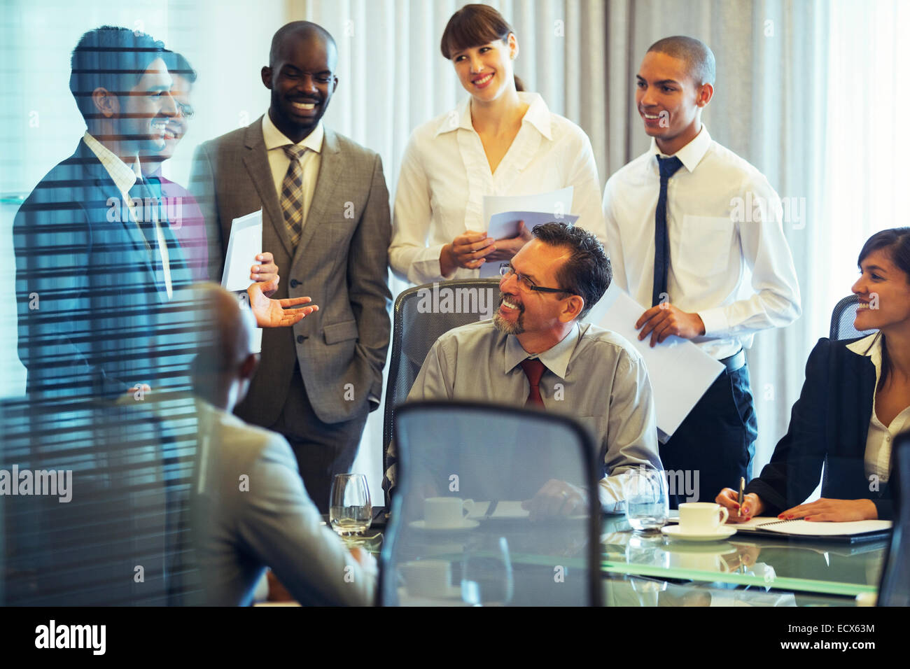 Business people smiling in conference room during business meeting Stock Photo