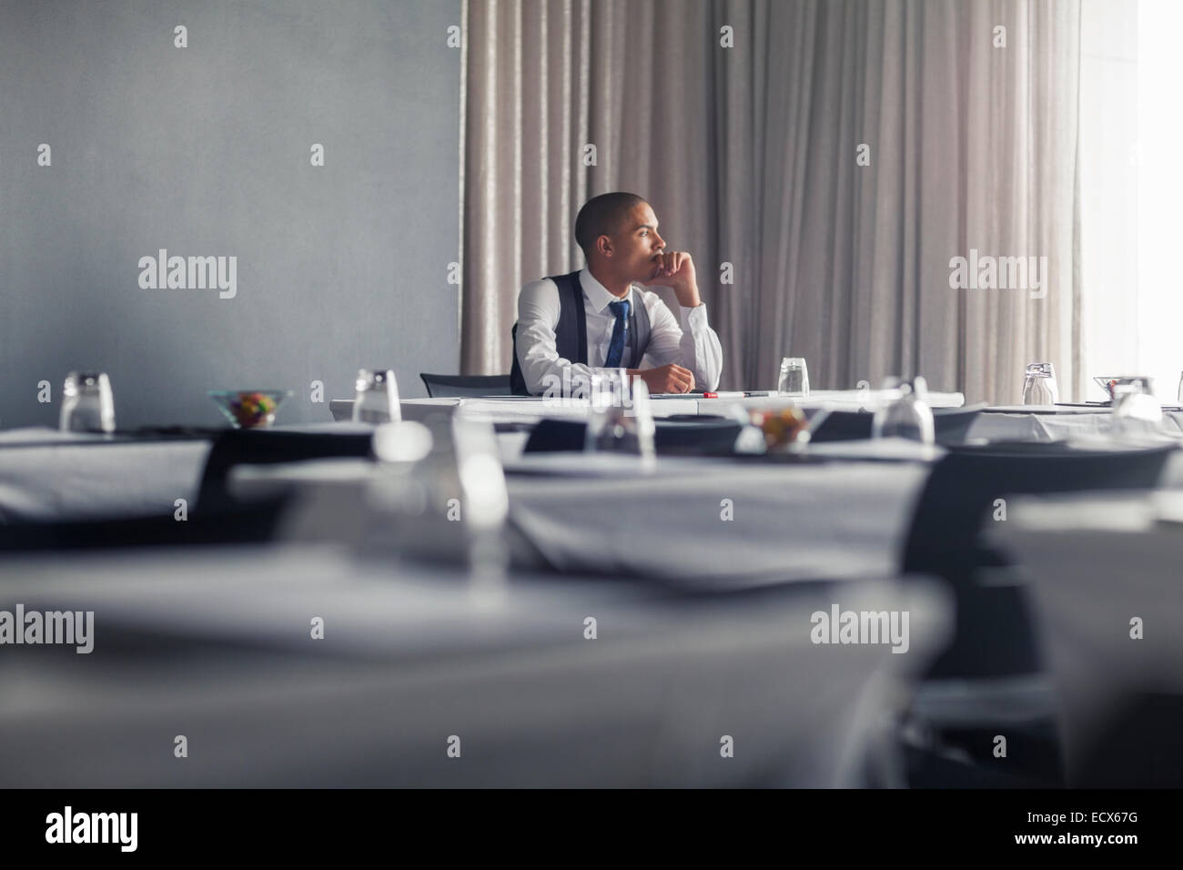 Portrait of young man sitting at table in empty conference room looking through window - Stock Image