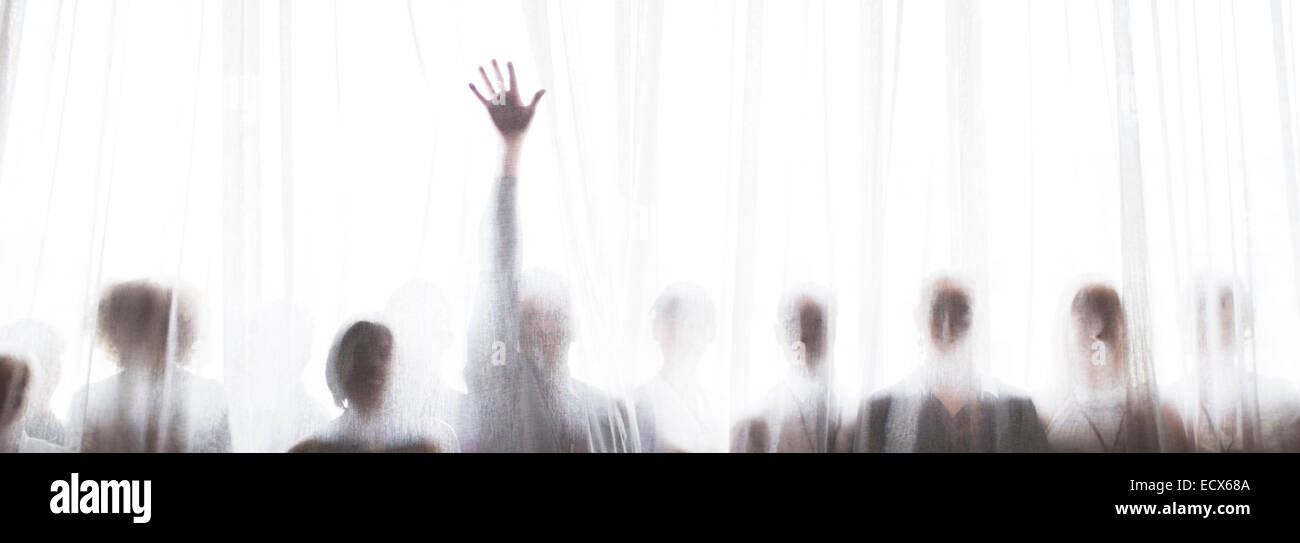Silhouette of people behind transparent curtain, one person rising hand - Stock Image