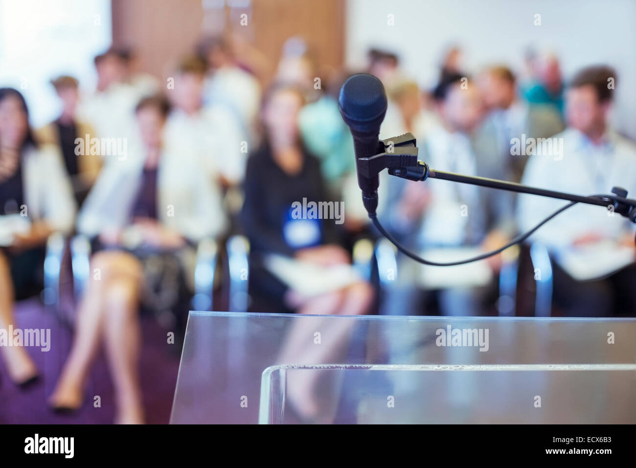 Close-up of microphone and transparent lectern with audience seen in blurred background - Stock Image