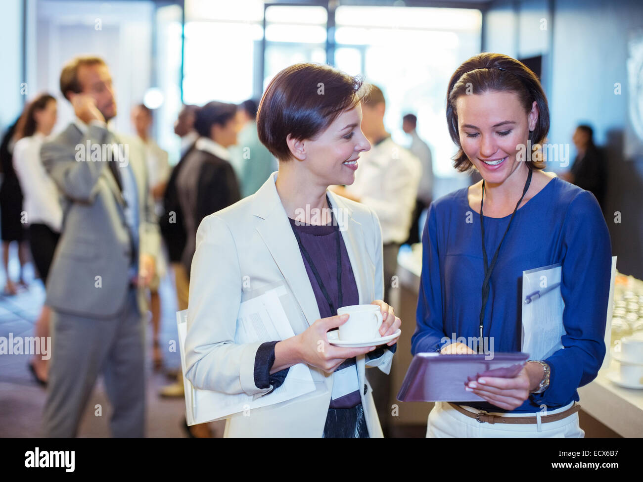 Portrait of two smiling women, talking in lobby of conference center during coffee break - Stock Image