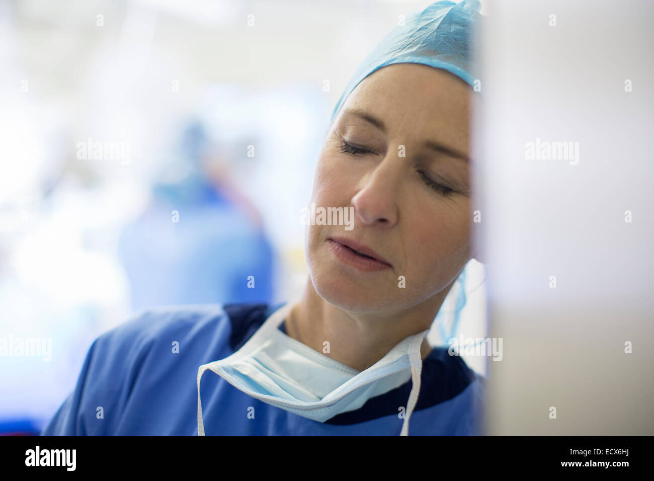 Female surgeon falling asleep in hospital - Stock Image