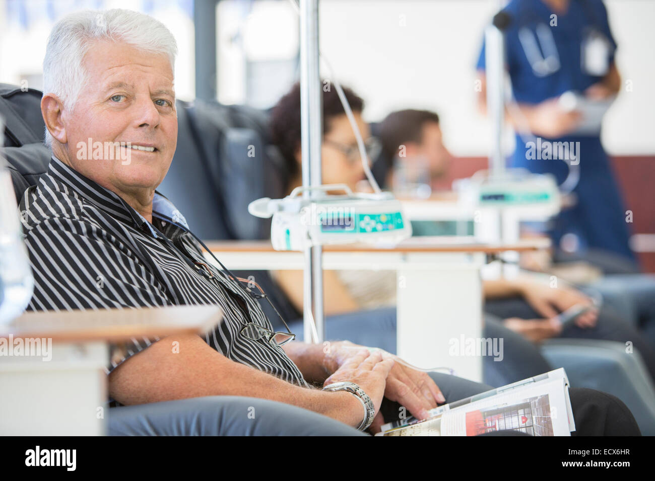 Smiling man undergoing medical treatment in outpatient clinic - Stock Image