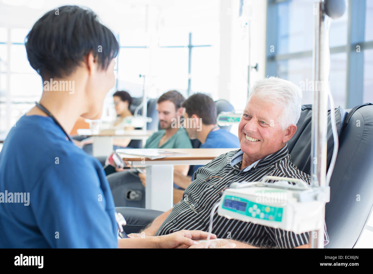 Senior patient undergoing medical treatment talking to doctor in outpatient clinic Stock Photo
