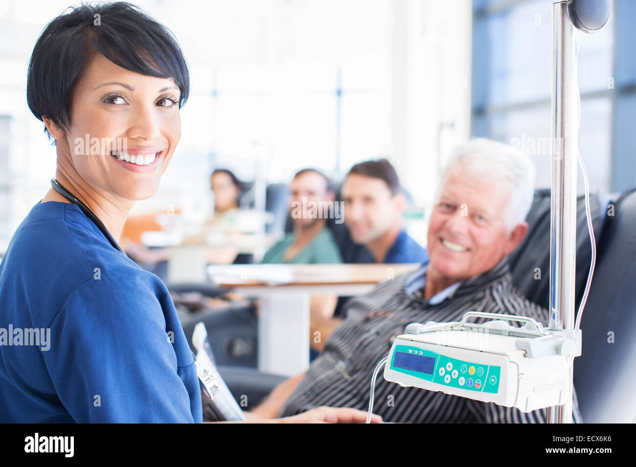 Portrait of smiling doctor assisting patient undergoing medical treatment in outpatient clinic - Stock Image