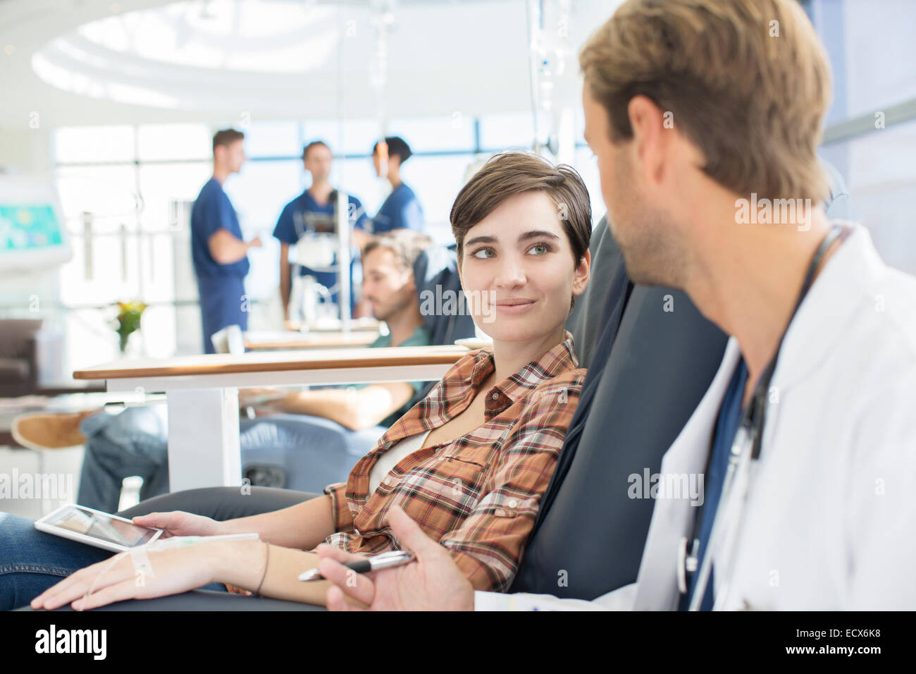 Doctor talking to patient undergoing medical treatment in outpatient clinic - Stock Image