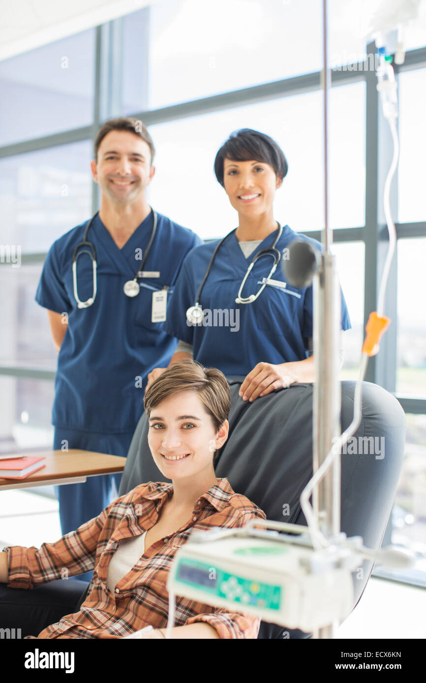 Smiling doctors standing by patient undergoing medical treatment in outpatient clinic - Stock Image