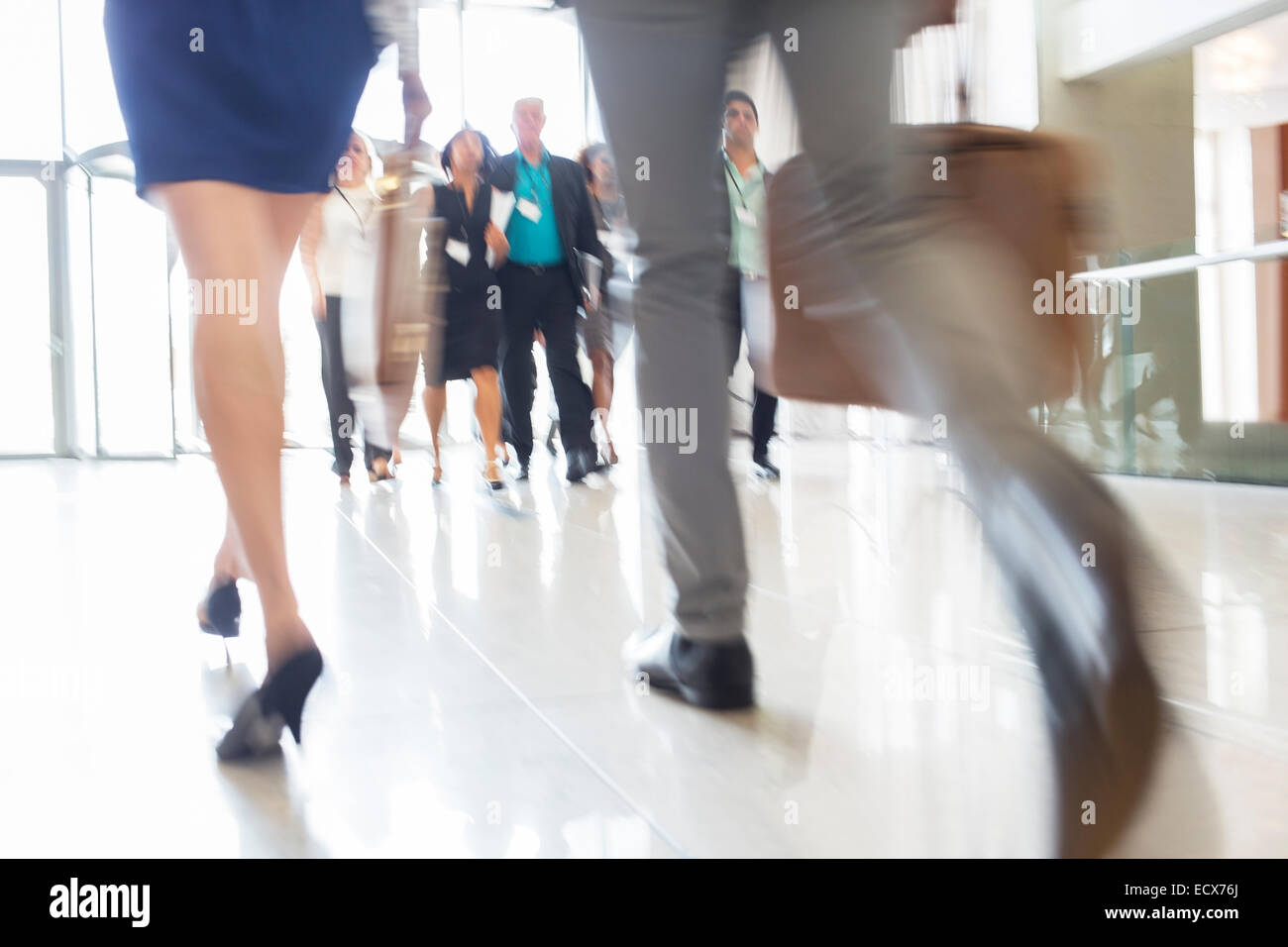 Legs of businesswoman and businessman carrying hand luggage walking through lobby of conference center - Stock Image