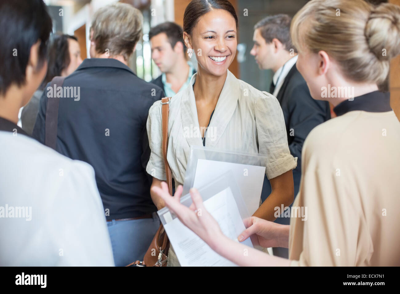Portrait of two smiling women holding files and talking, standing in crowded lobby - Stock Image