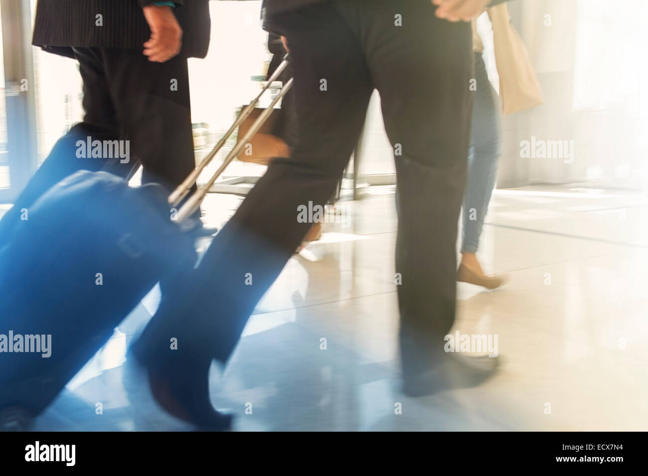 Cropped shot of two men walking side by side with trolley case - Stock Image