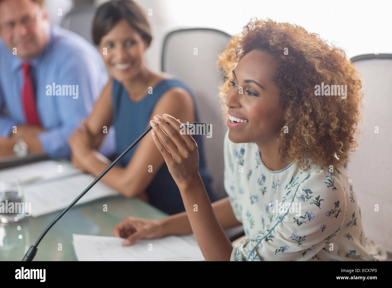 Beautiful woman sitting at conference table talking into microphone - Stock Image