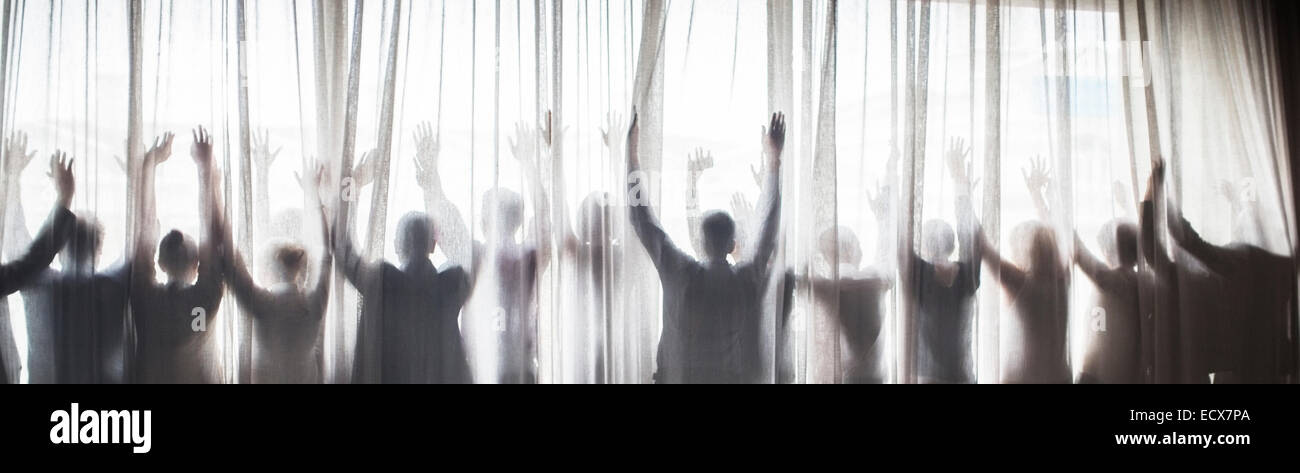 Silhouette of people raising hands behind transparent curtain - Stock Image