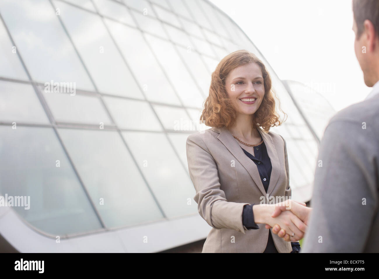 Business people shaking hands outdoors - Stock Image