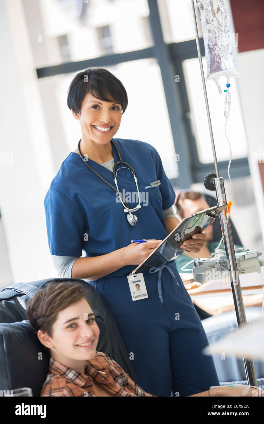 Female doctor posing with young patient receiving medical treatment in hospital ward - Stock Image