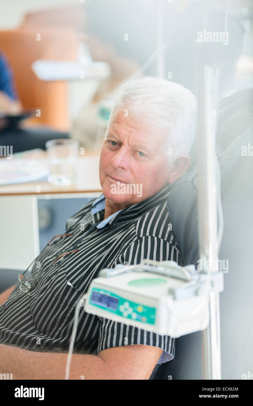 Senior man receiving intravenous infusion in hospital - Stock Image