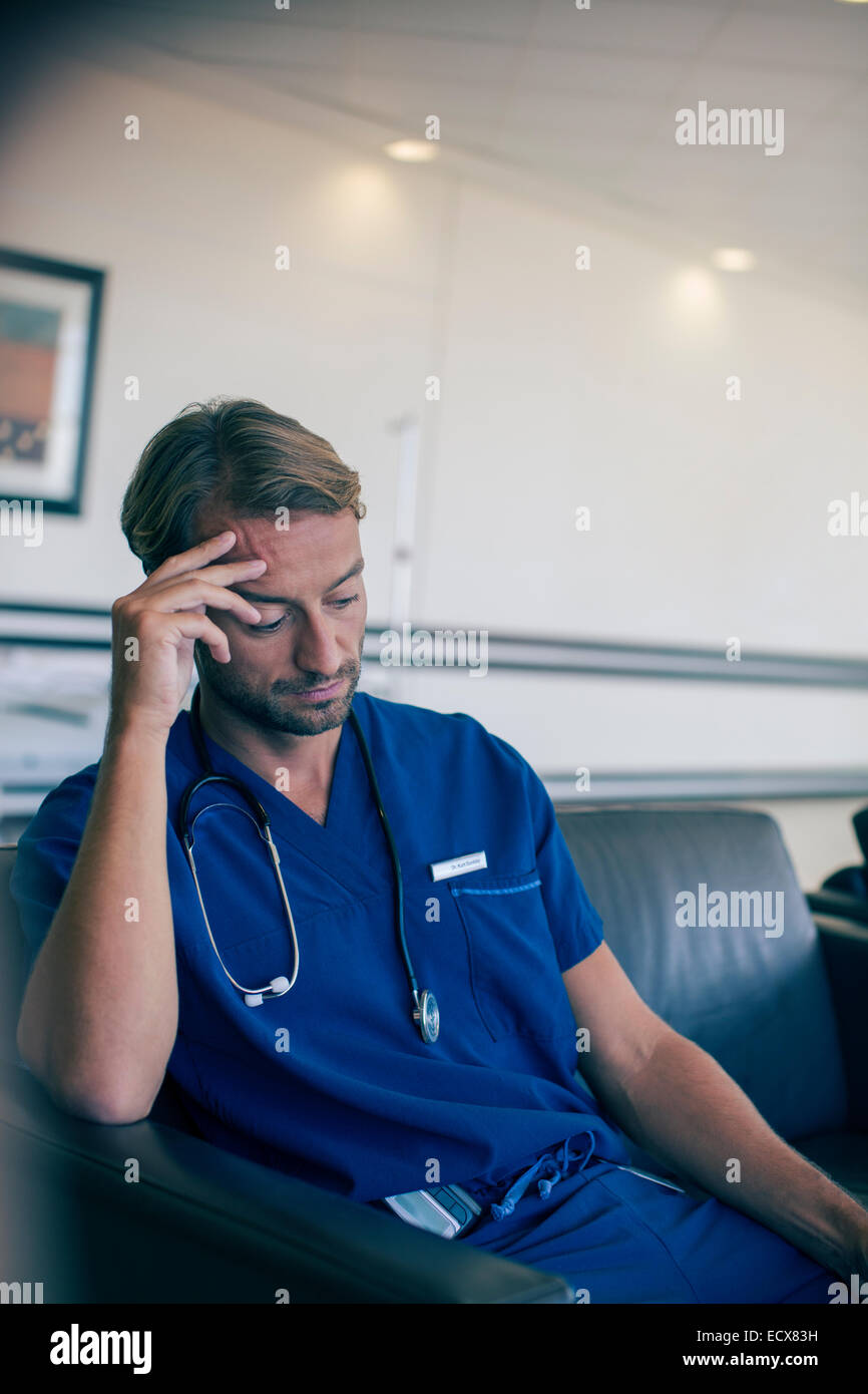 Male doctor sitting on sofa in hospital - Stock Image