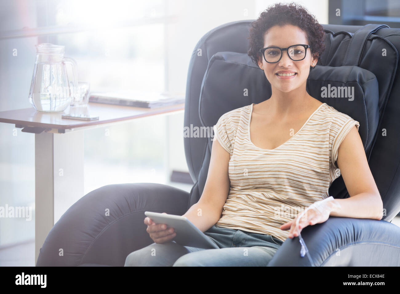Smiling patient holding tablet pc, undergoing medical treatment in outpatient clinic - Stock Image