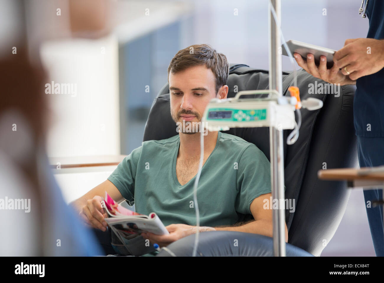 Patient reading magazine, undergoing medical treatment in outpatient clinic - Stock Image
