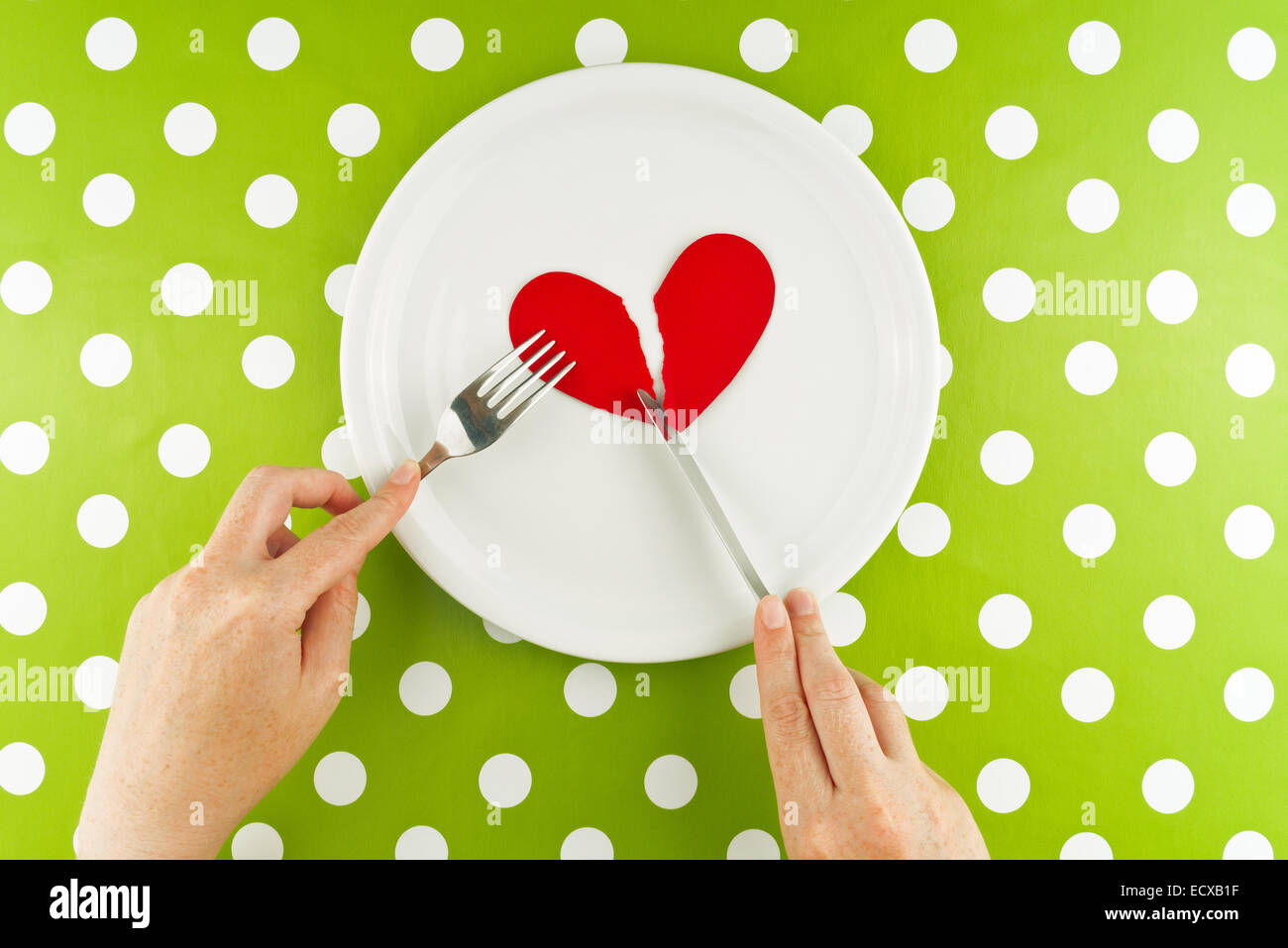 Woman eating broken heart on a white plate, top view. - Stock Image