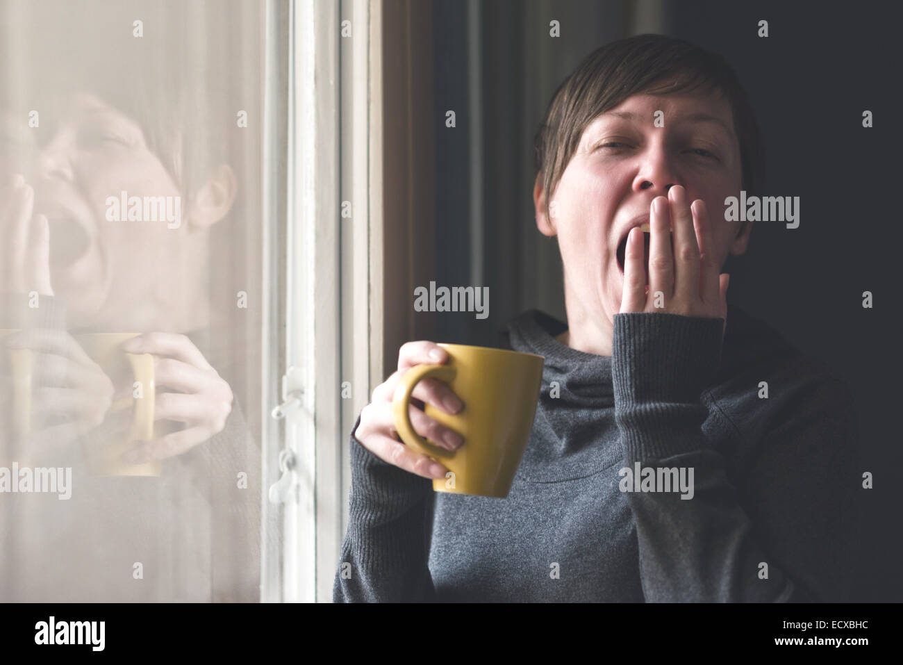 Beautiful sleepy caucasian adult woman drinking cup of coffee and yawning in the early morning. - Stock Image