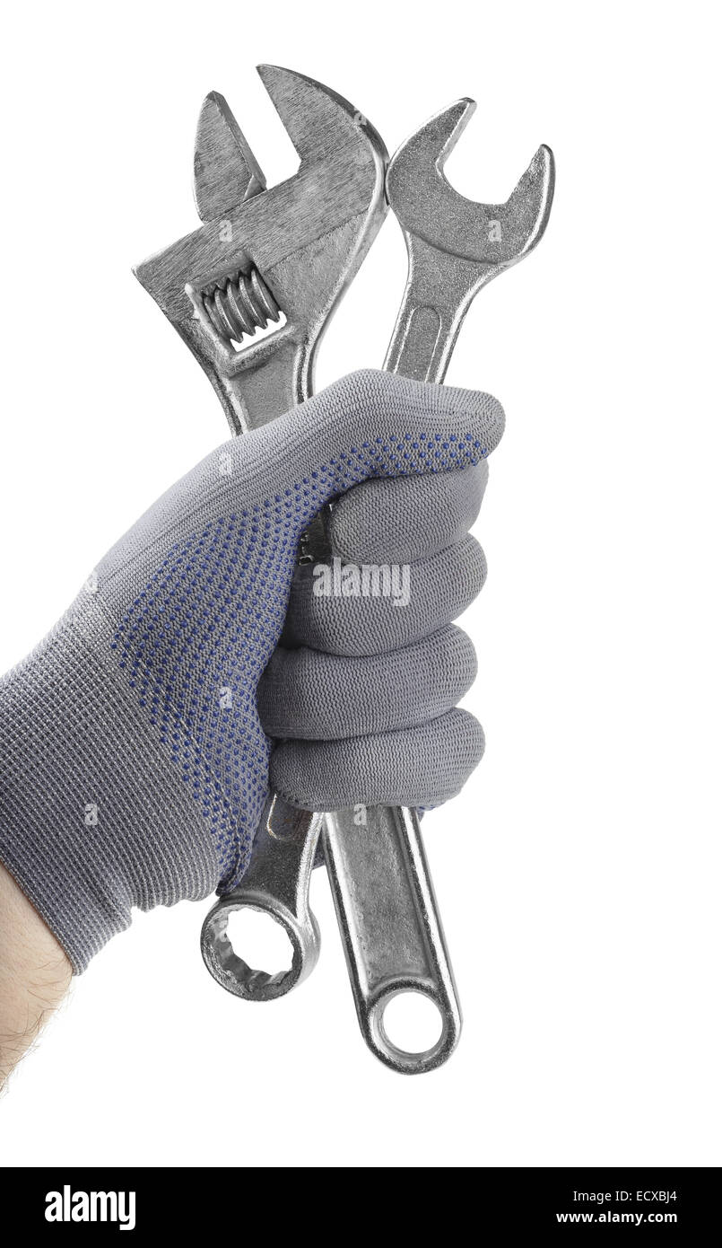 Gloved hand holding wrenches isolated on white - Stock Image