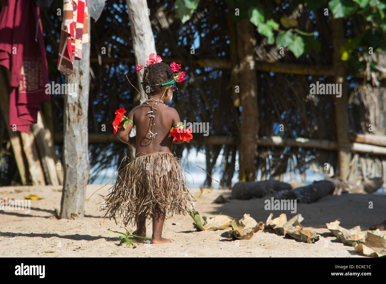 Melanesia, Papua New Guinea, Bismark Sea area, Tuam Island, Tuam village. Young girl in grass skirt dressed for - Stock Image